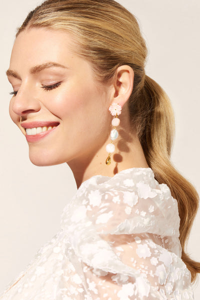 Thumbnail of model wearing the Daisy Chain Pearl Earrings. Whether you're walking down the aisle or just strolling through your neighbourhood, these mixed-media charmers have got you covered. The linked column earrings feature pink conch flower tops, pink opal and morganite beads, freshwater pearls and gold-plated brass drops.
