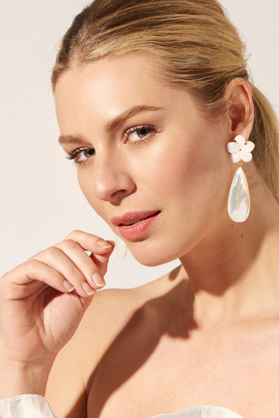 Thumbnail of model wearing the Queen Conch Earrings. <Insert crown emoji> You'll rule the spring garden party and nail those relaxed beach bash vibes in our flattering peach shell earrings. With hand-carved pale pink conch flower tops and iridescent mother-of-pearl teardrops.