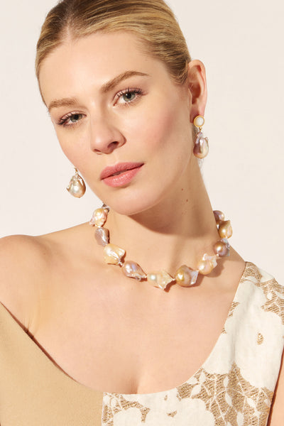 Thumbnail of model wearing the Estate Pearl Necklace In Pink. Classic meets bold (and lives happily ever after) in Lizzie's stunning vision of a single-strand pearl necklace. Featuring extra large peach and lavender baroque pearls, tied with pink silk knots and a gold-plated hook closure.