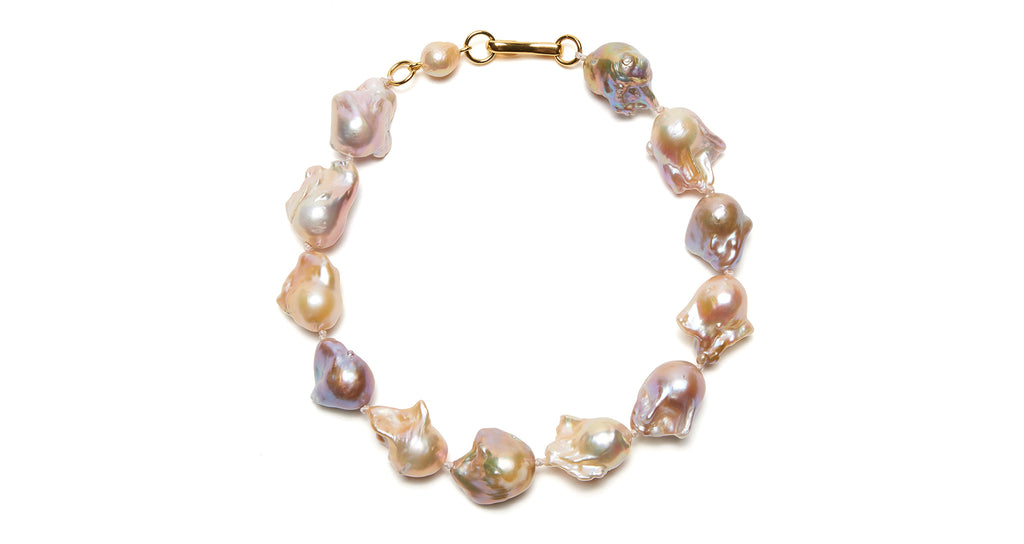 Full view of Estate Pearl Necklace In Pink. Classic meets bold (and lives happily ever after) in Lizzie's stunning vision of a single-strand pearl necklace. Featuring extra large peach and lavender baroque pearls, tied with pink silk knots and a gold-plated hook closure.