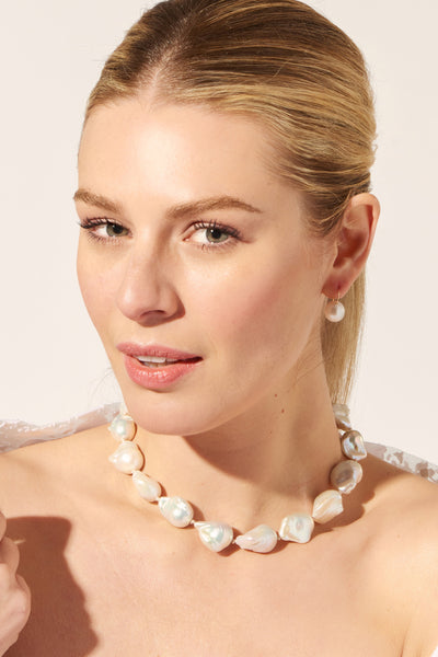Thumbnail of model wearing the Estate Pearl Necklace In White. Elegant meets organic (and lives happily ever after) in our updated iteration of the timeless single-strand pearl necklace. Featuring large white baroque pearls, pink silk knots and a gold-plated hook closure.