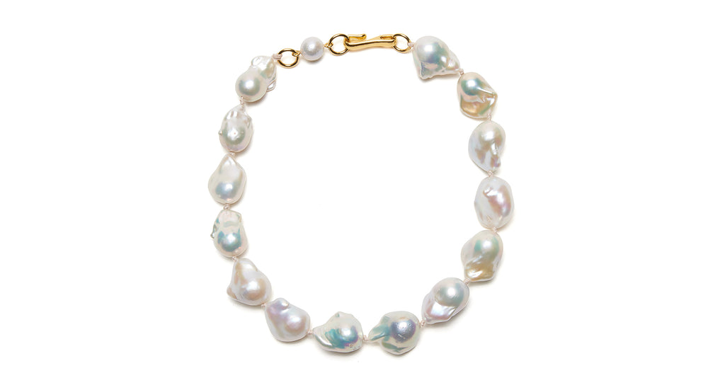 Full view of Estate Pearl Necklace In White. Elegant meets organic (and lives happily ever after) in our updated iteration of the timeless single-strand pearl necklace. Featuring large white baroque pearls, pink silk knots and a gold-plated hook closure.
