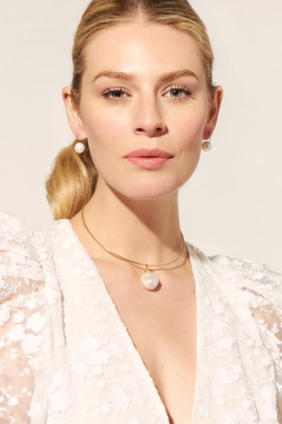Thumbnail of model wearing the Best Lady Necklace In Pearl. For the girl who wants to streamline her style while ensuring all eyes remain on her, we present our sleek gold-fill wire collar with extra large white baroque pearl pendant.