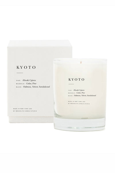 Thumbnail close-up of Kyoto Scented Candle. The tree-lined streets and wooden architecture in Kyoto inspired this meditative blend of Hinoki cypress, cedar, sandalwood, vetiver, and pine.  Candles are hand-poured in Brooklyn, New York with soy wax for a clean burn. With double cotton braided wicks primed with vegetable wax and fine perfume oils and essential oils sourced from around the world. Housed in elegant textured boxes and screenprinted glass tumblers.