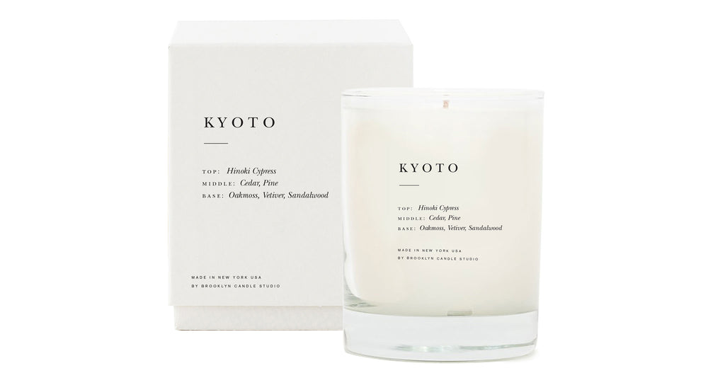 Full view of Kyoto Scented Candle. The tree-lined streets and wooden architecture in Kyoto inspired this meditative blend of Hinoki cypress, cedar, sandalwood, vetiver, and pine.  Candles are hand-poured in Brooklyn, New York with soy wax for a clean burn. With double cotton braided wicks primed with vegetable wax and fine perfume oils and essential oils sourced from around the world. Housed in elegant textured boxes and screenprinted glass tumblers.