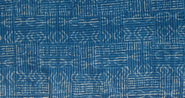 Pattern detail of Batik Indigo Dhurrie Rug. Lizzie found this hand-woven deep blue rug in Rajasthan, India and fell in love with its modern, muted block-printed patterns. This durable rug is perfect for kitchens and entryways.