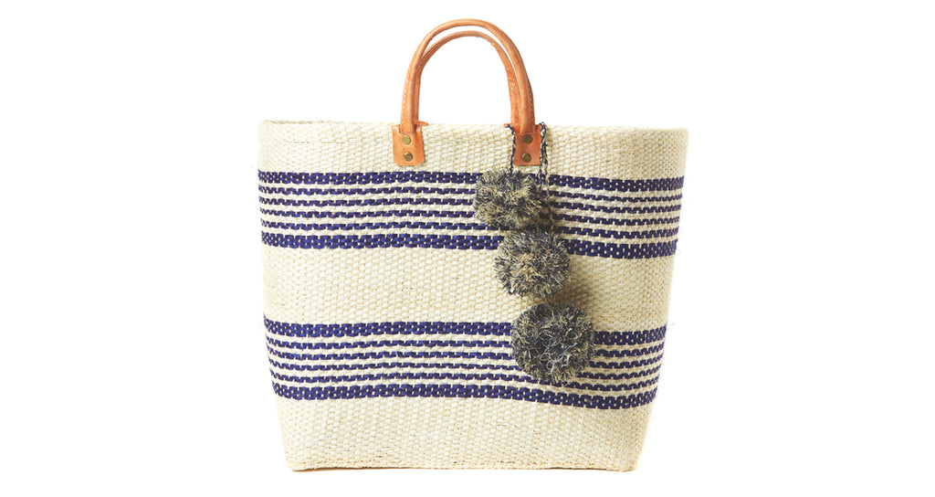 Handwoven natural and navy striped sisal and seagrass with raffia pom poms, inside pocket an...