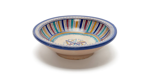 Full view of Fes Serving Dish In Primavera. Serve up some international flair at your next dinner party with this one-of-a-kind hand-painted clay serving bowl from Morocco.