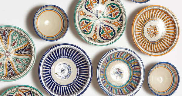 Studio shot of Fes Dishes, including the Fes Serving Dish In Primavera. Serve up some international flair at your next dinner party with this one-of-a-kind hand-painted clay serving bowl from Morocco.