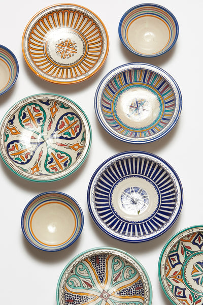 Thumbnail studio shot of Fes Dishes, including the Fes Serving Dish In Tangerine. Serve up some international flair at your next dinner party with this one-of-a-kind hand-painted orange clay serving bowl from Morocco.