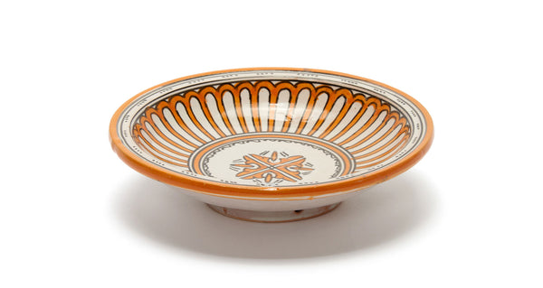 Full view of Fes Serving Dish In Tangerine. Serve up some international flair at your next dinner party with this one-of-a-kind hand-painted orange clay serving bowl from Morocco.
