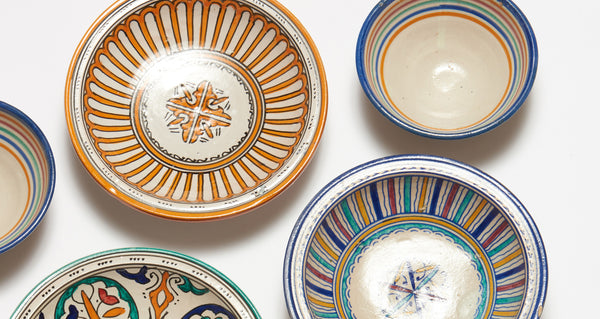 Studio shot of assorted Fes dishes, including Fes Bowl In Prisma. the Add some international flair to your tabletop with this fun rainbow striped clay bowl from Morocco.