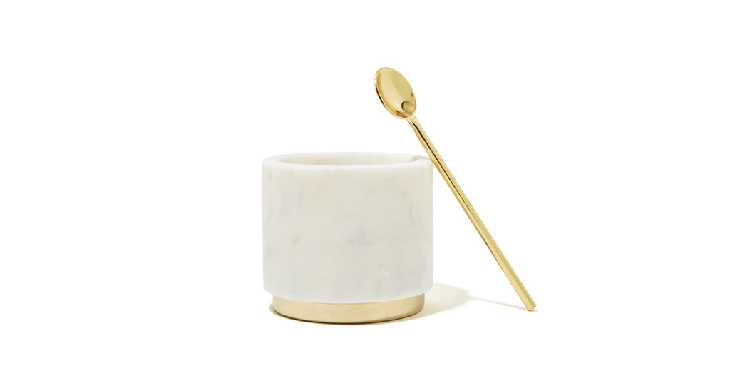 Full view of Mara Marble + Brass Sugar Pinch Pot. Constructed of hollowed white marble blocks and finished with a brass base + spoon, this dish makes a coolly classic addition to any counter or tabletop. Pair this diminutive beauty with the Hawkins creamer for a match made in coffee service heaven.