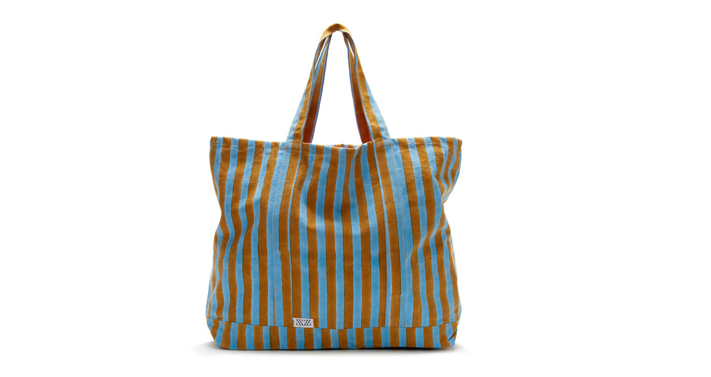 Full view of Oversized Striped Tote. This massive and durable canvas tote will be the one you reach for all summer long-- for beach days, farmer's market runs, and overnight stays. The cheery stripes were block-printed by hand in Jaipur.
