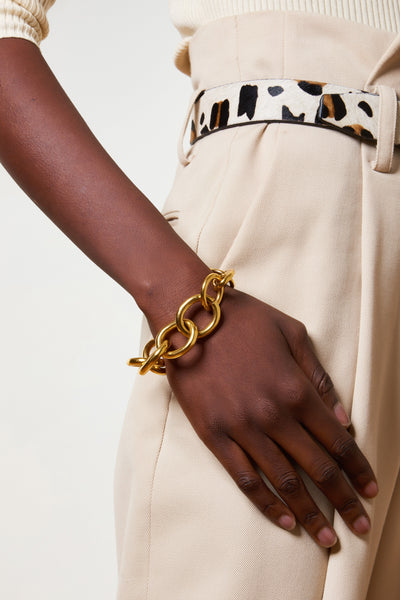 Thumbnail of model wearing the Porto Chain Bracelet. Talk about a wardrobe essential. The versatility of a classic chain bracelet cannot be overestimated; we think our gold-plated large-link version with an oversized lobster clasp is prep perfection.