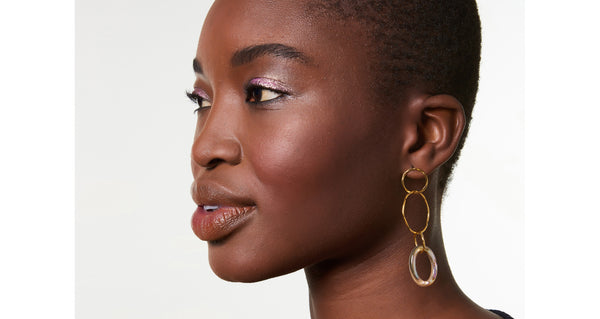 Model wearing The Lake City Earrings In Abalone. You'll love the way these elegant stunners catch the light when the gold vermeil linked hoops sway as you move. Choose a pair of our organic wire earrings with either hanging freshwater pearls or iridescent abalone rings.