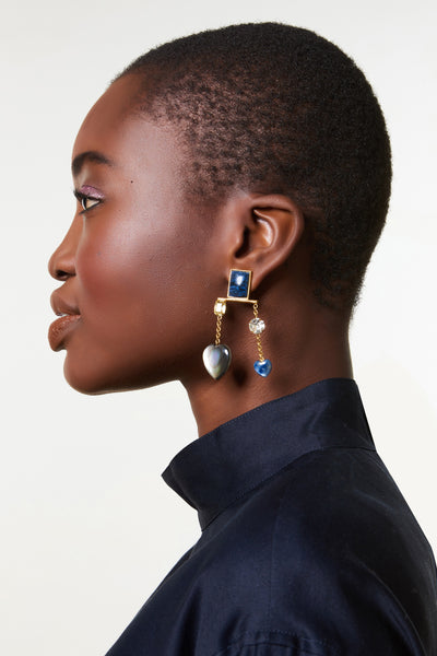Thumbnail of model wearing the Lucky Earrings. We're up all night to get lucky in gold-plated chandelier statement earrings awash in dramatic tones of blue. With navy quartzite rectangle stone tops and hanging vermeil chains with faceted crystals, black mother-of-pearl, kyanite, and citrine hearts.