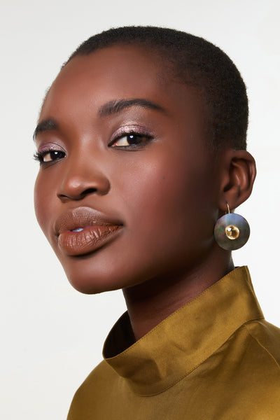 Thumbnail of model wearing the Taj Disc Earrings. Small yet attention-getting, these gold vermeil earrings with black mother-of-pearl discs and faceted citrine stones will become your new symbols of wearable luxury.