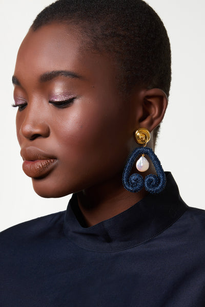 "Thumbnail of model wearing the Scroll Earrings In Navy. Here's a fresh way to wear pearls -- hang them inside our navy metallic embroidered ""scroll"" earrings for an eye-catching mix of materials.  With gold-plated ""nautilus"" tops to play up that sophisticated sea vibe."