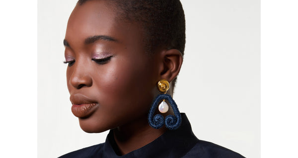 "Model wearing the Scroll Earrings In Navy. Here's a fresh way to wear pearls -- hang them inside our navy metallic embroidered ""scroll"" earrings for an eye-catching mix of materials.  With gold-plated ""nautilus"" tops to play up that sophisticated sea vibe."