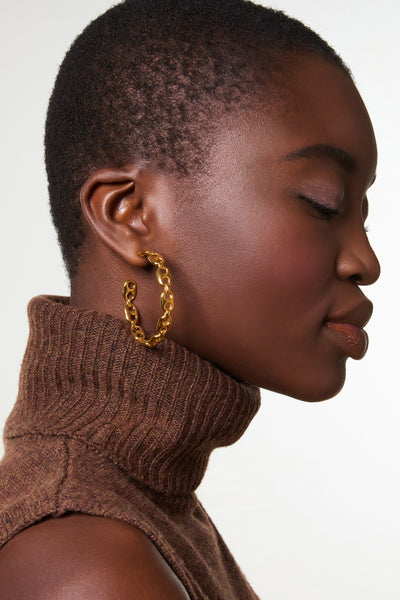 Thumbnail of model wearing Chain Link Hoop Earrings. Love the look of chain link? We've punctuated your everyday hoop earrings with organic link shapes for an edgy and elevated take on a wardrobe classic.