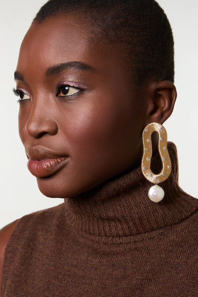 Thumbnail of model wearing the Escher Earrings In Gold. This is not an optical illusion -- these hand-woven metallic thread abstract shape earrings are indeed your new must-have statement accessory. With glass beads and hanging freshwater pearl drops.
