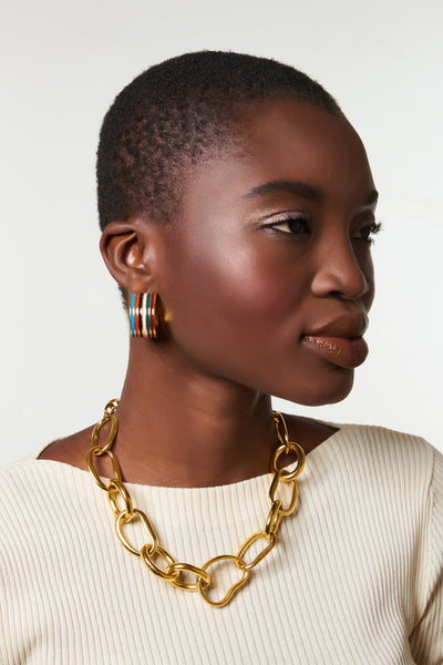 Thumbnail of model wearing the Margot Hoops In Rainbow. Nothing wrong with chasing rainbows. You'll be beaming confidence in this unique pair of wide gold-plated hoop earrings painted with multicolor striped enamel.