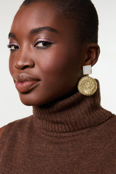 Thumbnail of model wearing the Golden Mala Earrings. Set your intentions to stand out this season, in these bold gold-plated earrings with hanging hand-woven metallic drops and square mother-of-pearl tops.