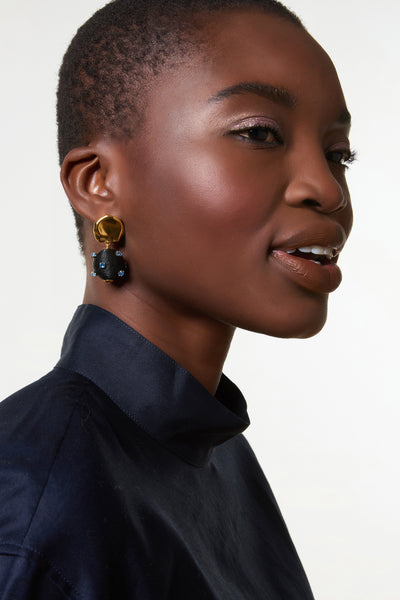 "Thumbnail of model wearing the Sparkler Earrings In Midnight. Ignite a stylish spark at your next event in the gold-plated ""coin"" top earrings with hanging black silk cord beads and tiny blue glass orbs."
