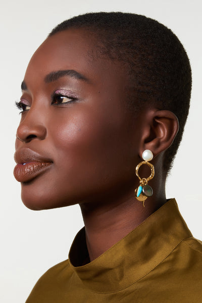 Thumbnail of model wearing the Alchemy Earrings. Turn a basic outfit into a statement look with pearl-topped earrings featuring a winning mix of hanging turquoise, pearl and gold-plated charms.  Voila! Now that's a transformation we can believe in.