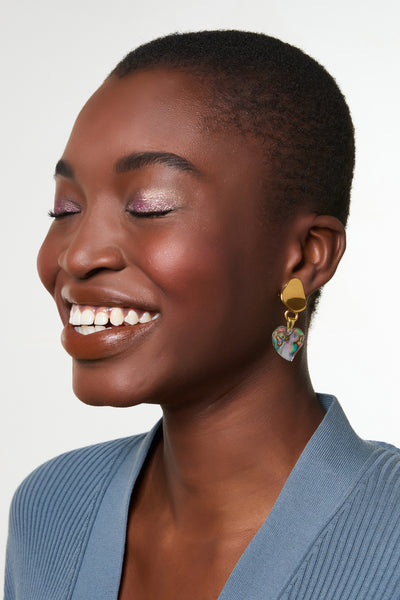 Thumbnail of model wearing the Abalone Heart Earrings. Have your heart set on wearing the grooviest earrings this season? Look no further than this gold-plated abstract pair, with hanging abalone heart charms that shine with a lustrous iridescence.