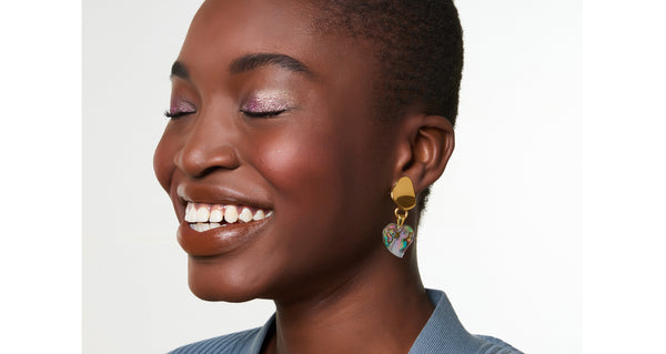 Model wearing the Abalone Heart Earrings. Have your heart set on wearing the grooviest earrings this season? Look no further than this gold-plated abstract pair, with hanging abalone heart charms that shine with a lustrous iridescence.