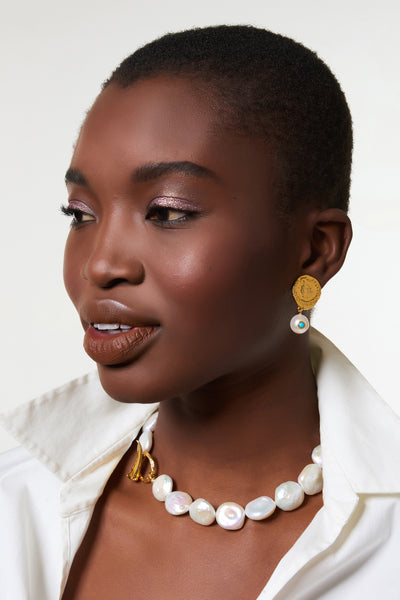 Thumbnail of model wearing the Court Earrings. Hold court in the extremely chic cast antique coin earrings. Accentuated with hanging freshwater pearls set with carnelian and turquoise cabochons, this is a truly timeless pair.