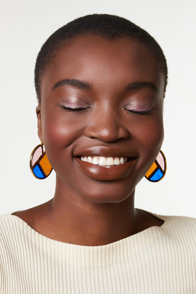 Thumbnail of model wearing the Glass Mosaic Hoops. Old world craft meets contemporary style in gold-plated hoop earrings with hand-cut rose, tomato, and cobalt-colored graphic glass inlay.