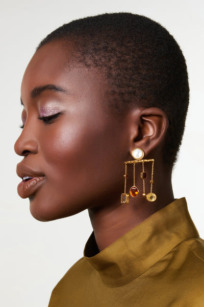 Thumbnail of model wearing the Libra Earrings. Tip the scales of style in these textured gold chandelier earrings. With pearl stone tops and hanging vermeil chains set with a delicate balance of faceted garnet, citrine and amethyst stones.