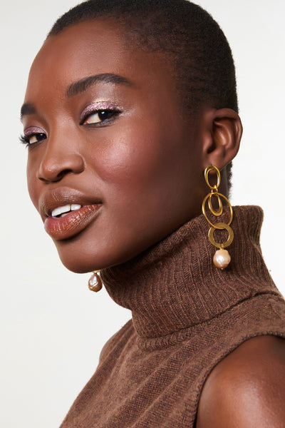 Thumbnail of model wearing the Wind Chime Earrings. These gold-plated linked earrings remind us of delicately balanced sculptural mobiles. Finished with champagne-colored freshwater pearl drops, you'll be a work of art at your next event.