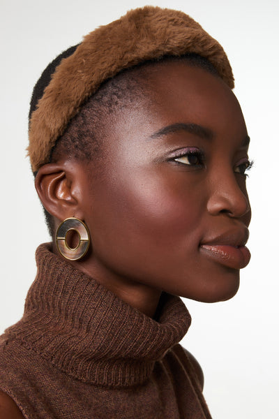 Thumbnail of model wearing Symmetry Earrings In Iridescent. How to bring some serious polish to all your basics? It's simple geometry in our oval stud earrings with bisected black mother-of-pearl inlay.