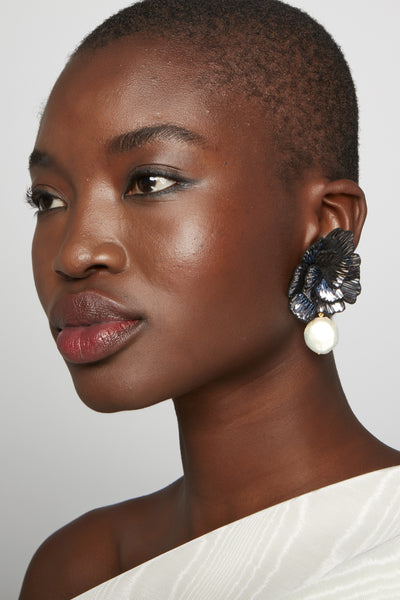 Thumbnail of model wearing Cosmic Flower Earrings. Looking for the perfect earrings for a big night out? Say it with flowers. These dramatic beauties feature hand-sewn navy and silver metallic blooms gilded with hanging freshwater pearls.