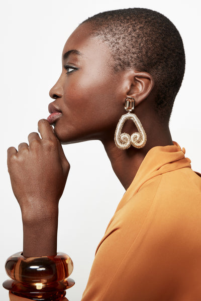 "Thumbnail of model wearing Scroll Earrings In Bronze. Embrace a return to the bronze age in our metallic brown embroidered ""scroll"" earrings with topaz crystal tops. We've forged this pair as clip-ons, for easy, light-as-a-feather wear."
