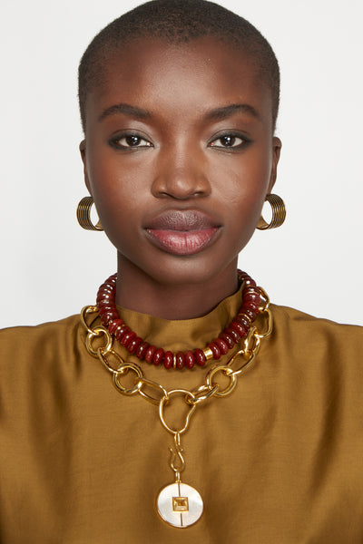 Thumbnail of model wearing Margot Hoops in Black. Hey, black magic woman. You'll cast quite the style spell in this unique pair of wide gold-plated hoop earrings painted with black striped enamel.