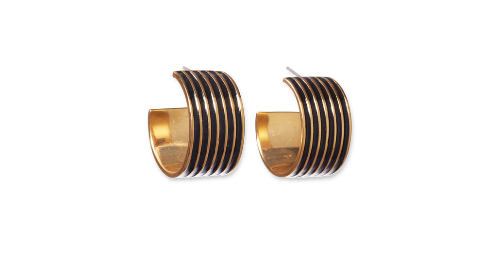 Full view of Margot Hoops In Black. Hey, black magic woman. You'll cast quite the style spell in this unique pair of wide gold-plated hoop earrings painted with black striped enamel.