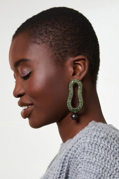 Thumbnail of model wearing the Escher Earrings In Olive. This is not an optical illusion -- these hand-woven metallic green thread abstract earrings are indeed your new must-have statement accessory. With glass beads and hanging peacock-colored pearl drops.