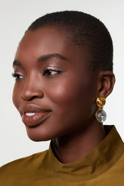 "Thumbnail of model wearing The Crown Earrings. You too can achieve royalty status in the small but mighty gold-plated ""nautilus"" earrings with faceted crystal round drops."