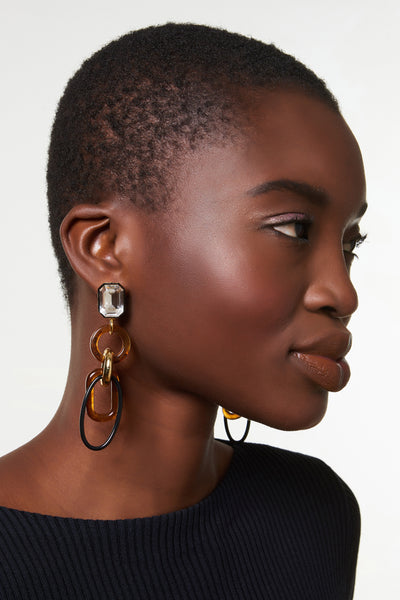 Thumbnail of model wearing Amber Fort Earrings. Our retro sculptural linked column earrings are ready to dress up black turtlenecks and finesse plain white T's everywhere. With crystal tops and hanging tortoise acrylic, black enamel, and gold-plated links. These beauties are clip-on, for easy and light-as-a-feather wear.