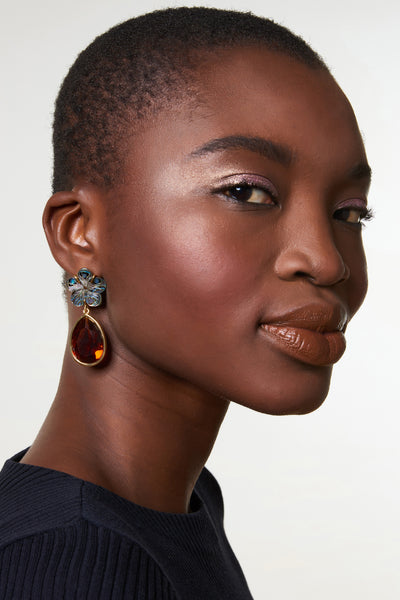 Thumbnail of model wearing the Lily Pad Earrings In Amber. The perfect accessory to punctuate any outfit, these earrings feature flower-shaped abalone tops and hanging amber-colored faceted glass teardrops. Fully elegant, completely wearable.
