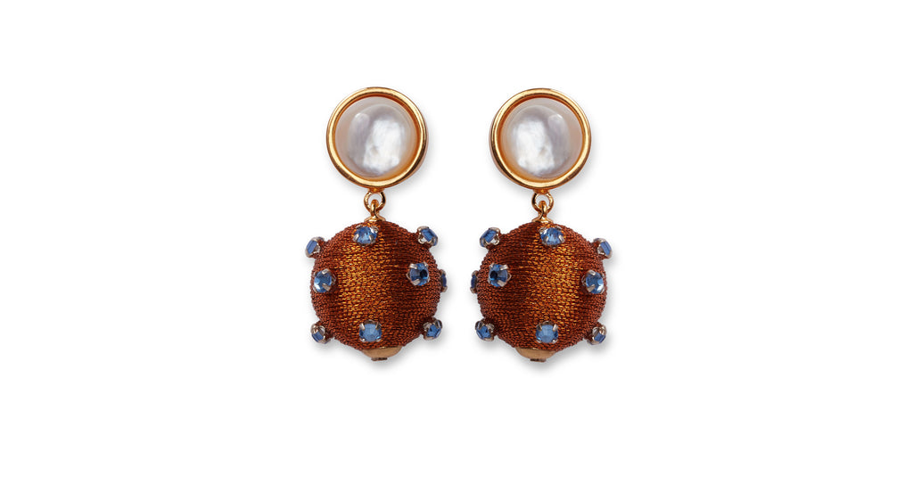Full view of Sparkler Earrings In Amber. Ignite a stylish spark at your next event in gold-plated earrings with hanging topaz silk cord beads and tiny blue glass orbs. Capped off with mother-of-pearl cabochons for an extra flash of brilliance.