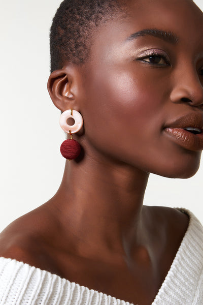 Thumbnail of model wearing Saffron Drop Earrings. Mad about saffron? Mellow out in the sweetest pink mother-of-pearl disc earrings with burgundy hand-woven drops.