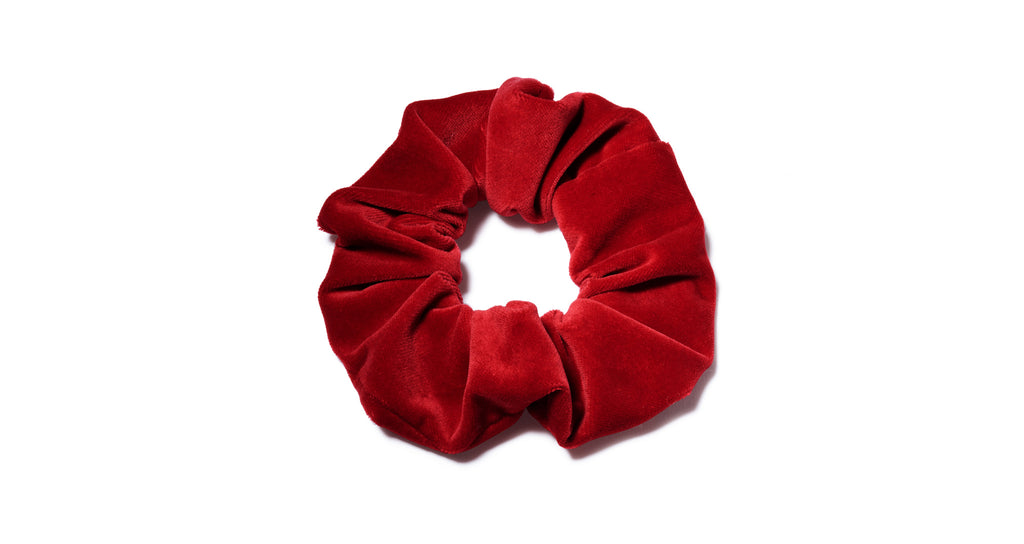 Full view of Velvet Scrunchie In Scarlet. All hail the return of the scrunchie, everyone's favorite fabric-covered elastic hair tie! Our version amps up the luxury factor in scarlet red velvet. The humble ponytail is about to get very stylish.