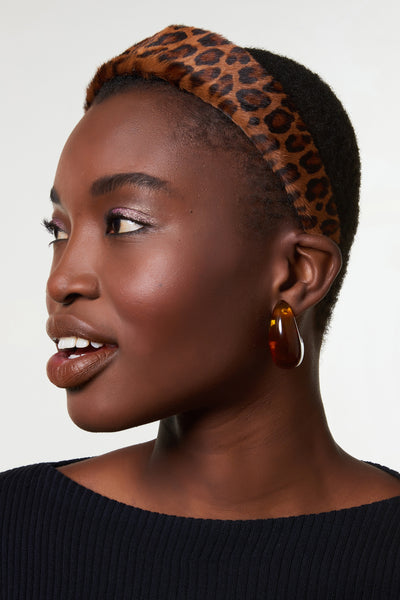 Thumbnail of model wearing the Safari Headband In Leopard. We've officially gone wild for this statement headband, featuring tan leopard-print calf hair.