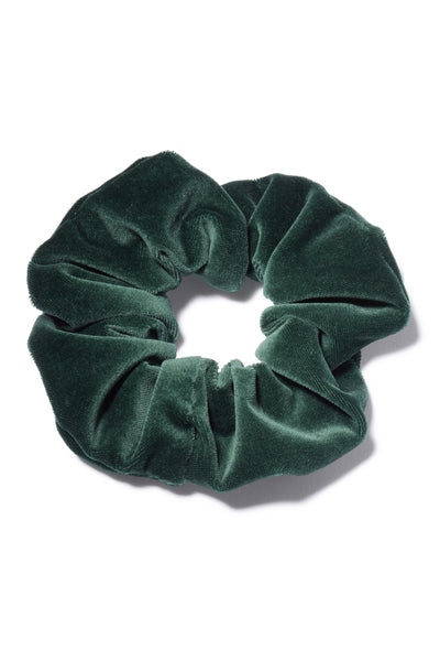 Thumbnail close-up of Velvet Scrunchie In Emerald. All hail the return of the scrunchie, everyone's favorite fabric-covered elastic hair tie! Our version amps up the luxury factor in emerald green velvet. The humble ponytail is about to get very stylish.